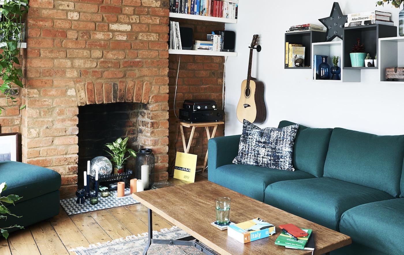 Ein Wohnzimmer mit grünem Sofa, farbigen Accessoires & einer frei liegenden Backsteinwand