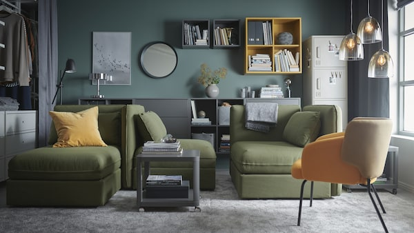 Ein Wohnzimmer mit grünen VALLENTUNA Modul-Bettsofas, grossen grauen Teppichen, gelben Schränken und Glashängeleuchten.