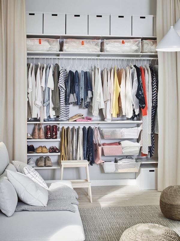 Ein Wohnzimmer mit offener Kleiderschranklösung hinter bodenlangen Gardinen