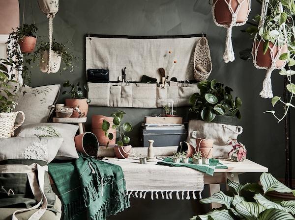 Ein Wohnzimmer mit Übertöpfen, Blumenampeln, Indoor-Gartenzubehör und Werkzeugschürzen aus der IKEA BOTANISK Kollektion.