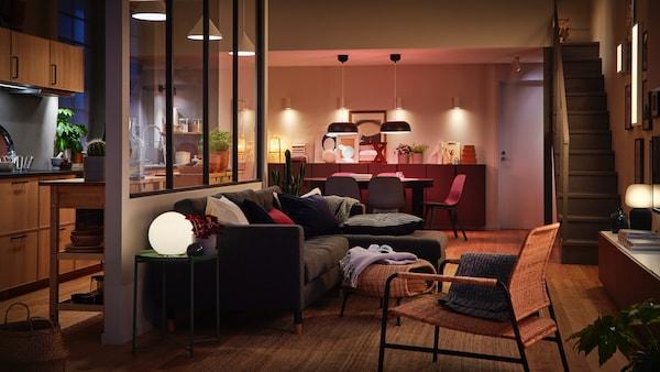 Ein wohnzimmer mit vielen Lichquellen in dunkler Atmosphäre eingerichtet.