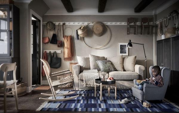 Ein Wohnzimmer u. a. mit einem GRÖNLID 2er-Bettsofa und einem GRÖNADAL Schaukelstuhl, daneben ein Kindersessel, in dem ein Kind sitzt.