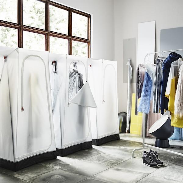 Ein Zimmer mit drei VUKU Kleiderschränken in Weiß zusammen mit einer Kleiderstange, an der Jeans, Pullover und eine Flokatijacke zu sehen sind.