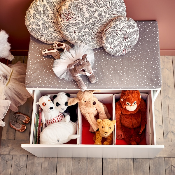 Eine Bank mit Kasten in Weiß mit einer Bankauflage in Grau mit weißen Punkten. Der Kasten steht offen. In ihm sind kleinere Fächer und viele Stofftiere zu sehen.