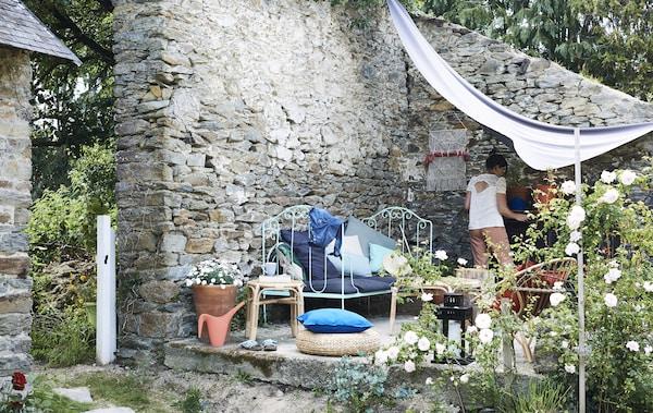 Eine Bank, Stühle und Ablagetische mit bunten Kissen in einem Gartenbereich mit Mauer