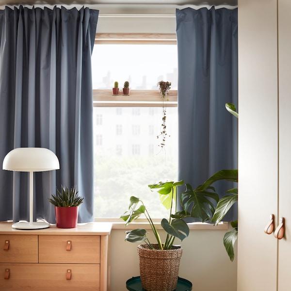 Eine BJÖRKSNÄS Kommode, hinter der an einem Fenster der BENGTA Gardinenschal zu sehen ist. Er bedeckt einen Großteil des Fensters.