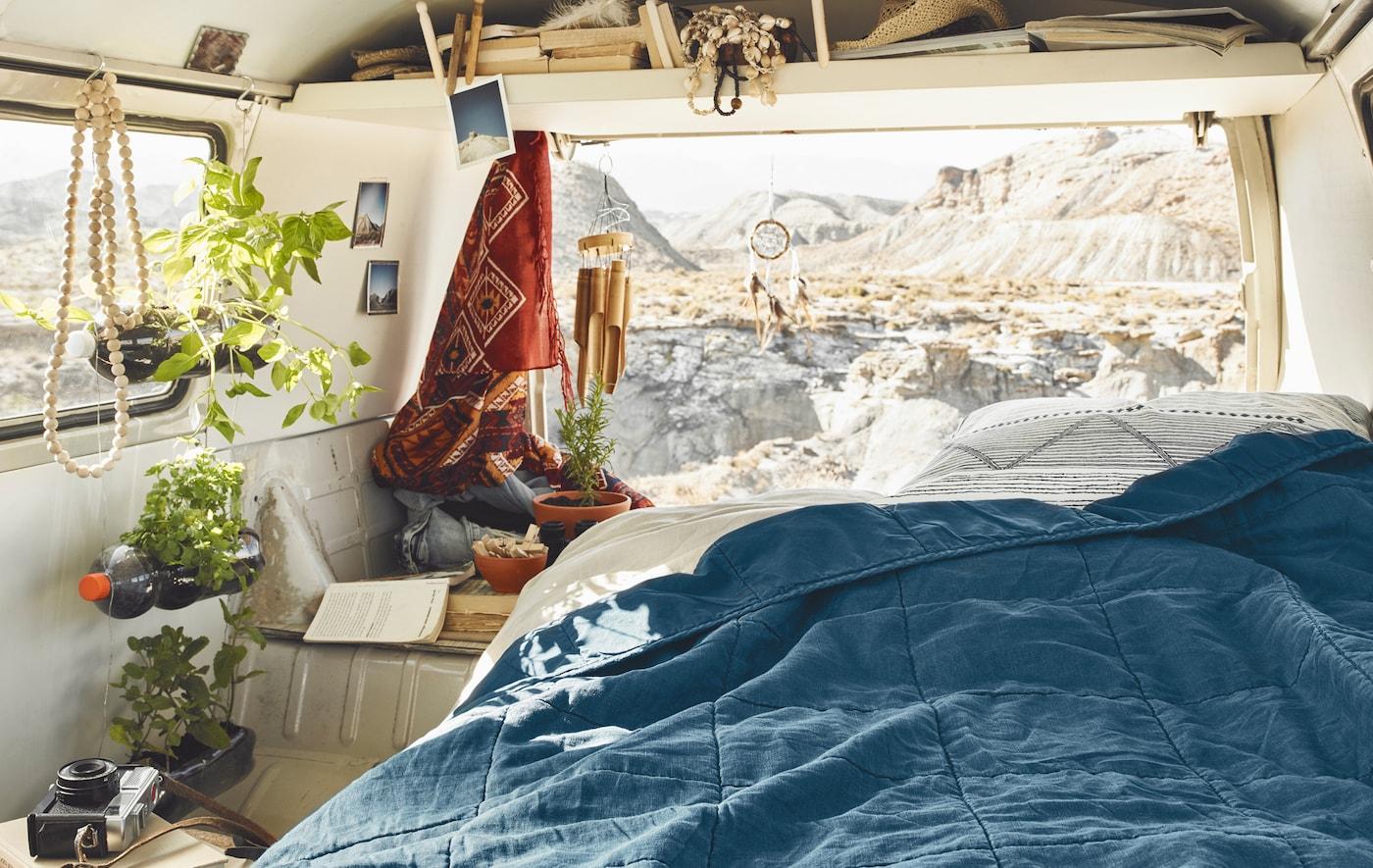 Eine blaue Tagesdecke in einem Wohnmobil mit Ausblick auf die Berge
