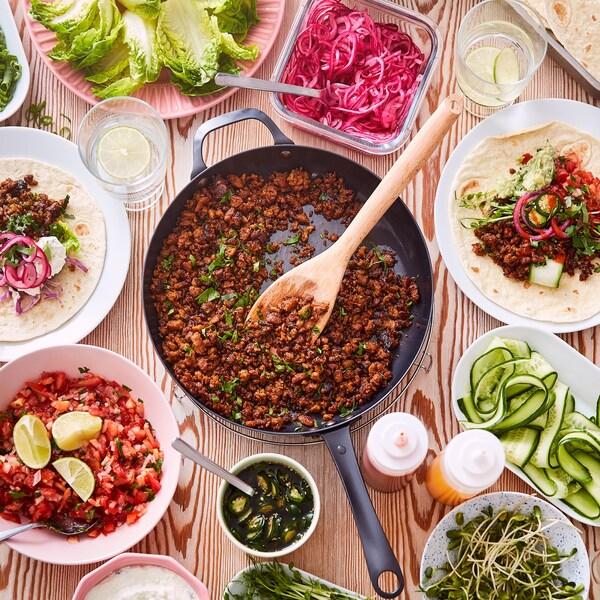 Eine Bratpfanne mit Tacohack aus dem VÄRLDSKLOK pflanzlichen Hack ist auf einem Holztisch zusammen mit Tellern und Schüsseln zu sehen, u. a. mit Pico de Gallo und Tortillas.