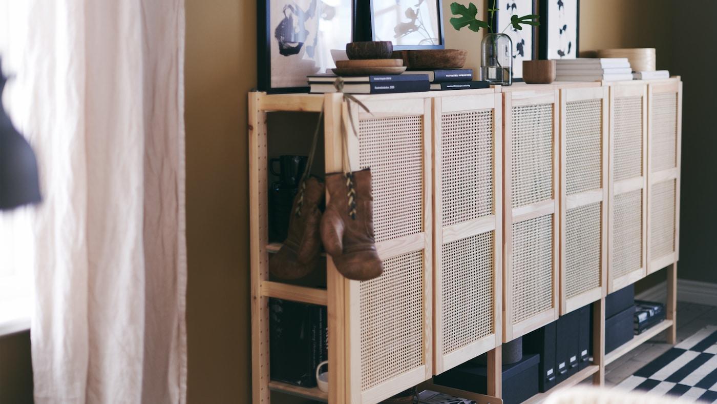 Eine breite Schrankkombination mit aus Bambus geflochtenen Türen steckt voller Bücher, Kunst und persönlichen Gegenständen.