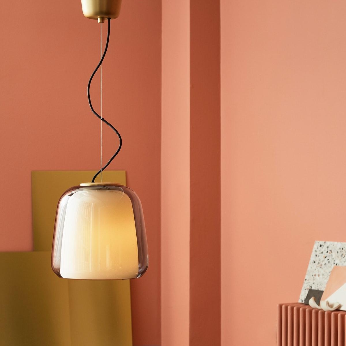 Eine doppelwandige Glashängeleuchte mit Messingdetails in einem rosafarben gestalteten Zimmer