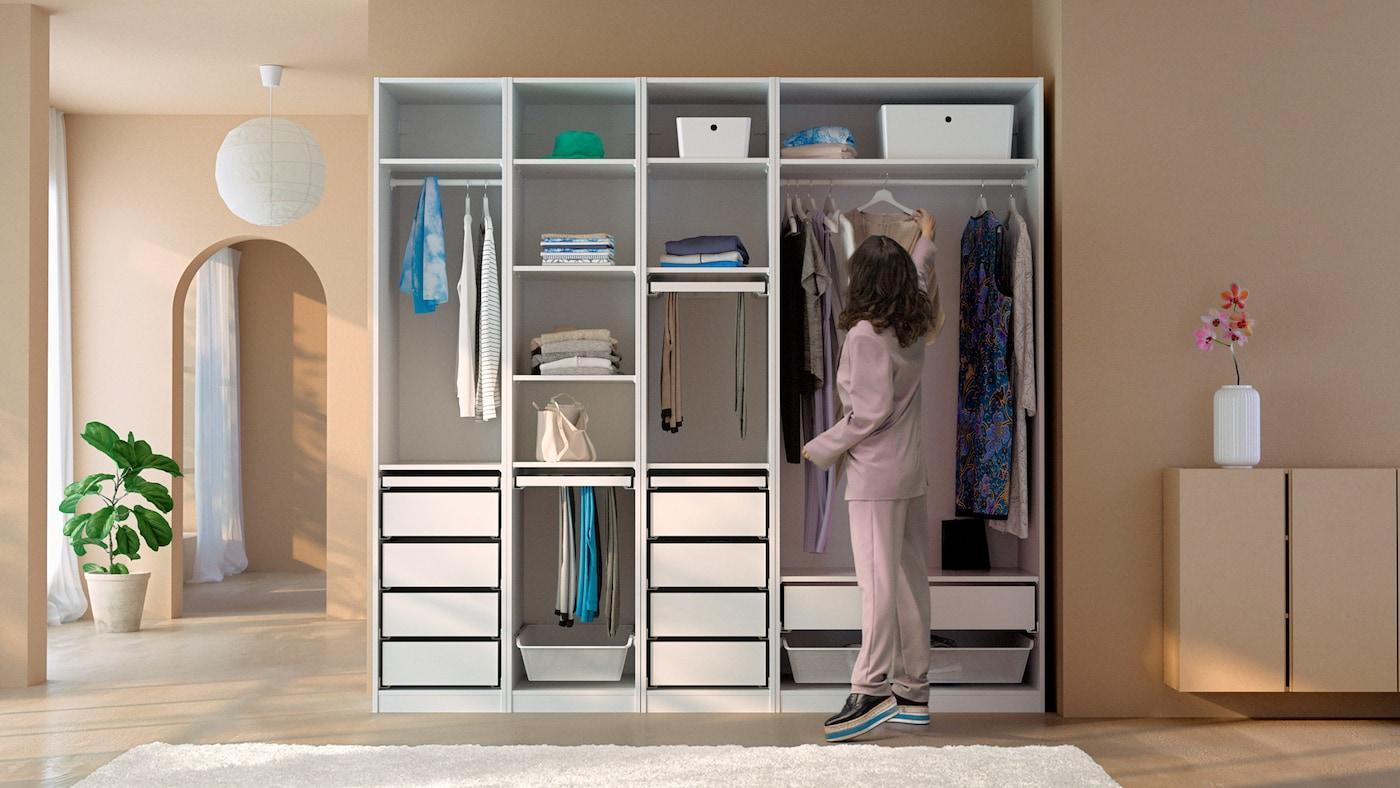 Eine dunkelhaarige Person hängt ein Kleid an eine Kleiderstange in eine weiße offene PAX Kleiderschrankkombination, die in einem Raum mit braunen Wänden steht.