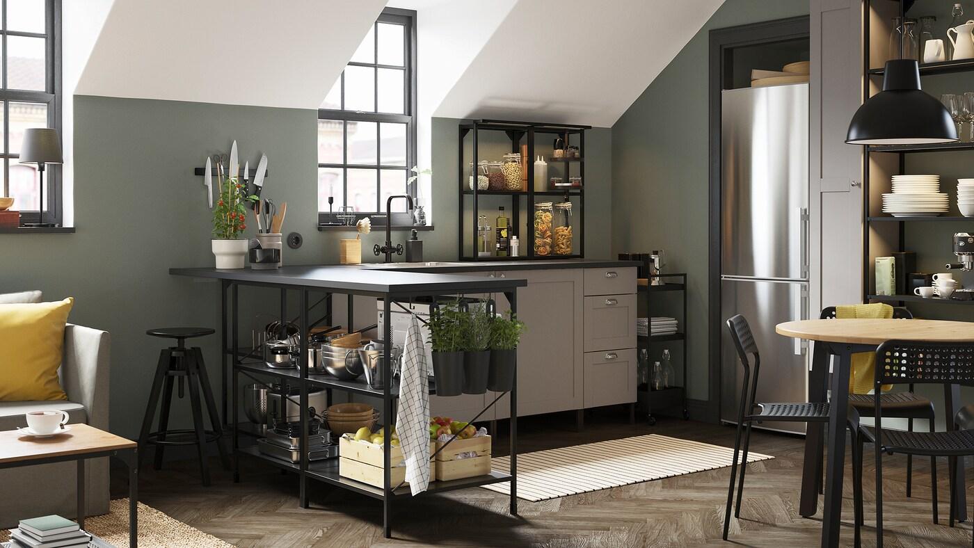 Eine Eckküche in Anthrazit/Grau, ein schwarzer Servierwagen, ein gestreifter Teppich und schwarze Behälter mit frischen Kräutern