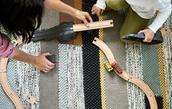 Eine Erwachsene setzt mit einem Kind auf einem Teppich eine Spielzeugeisenbahn aus Holz zusammen.