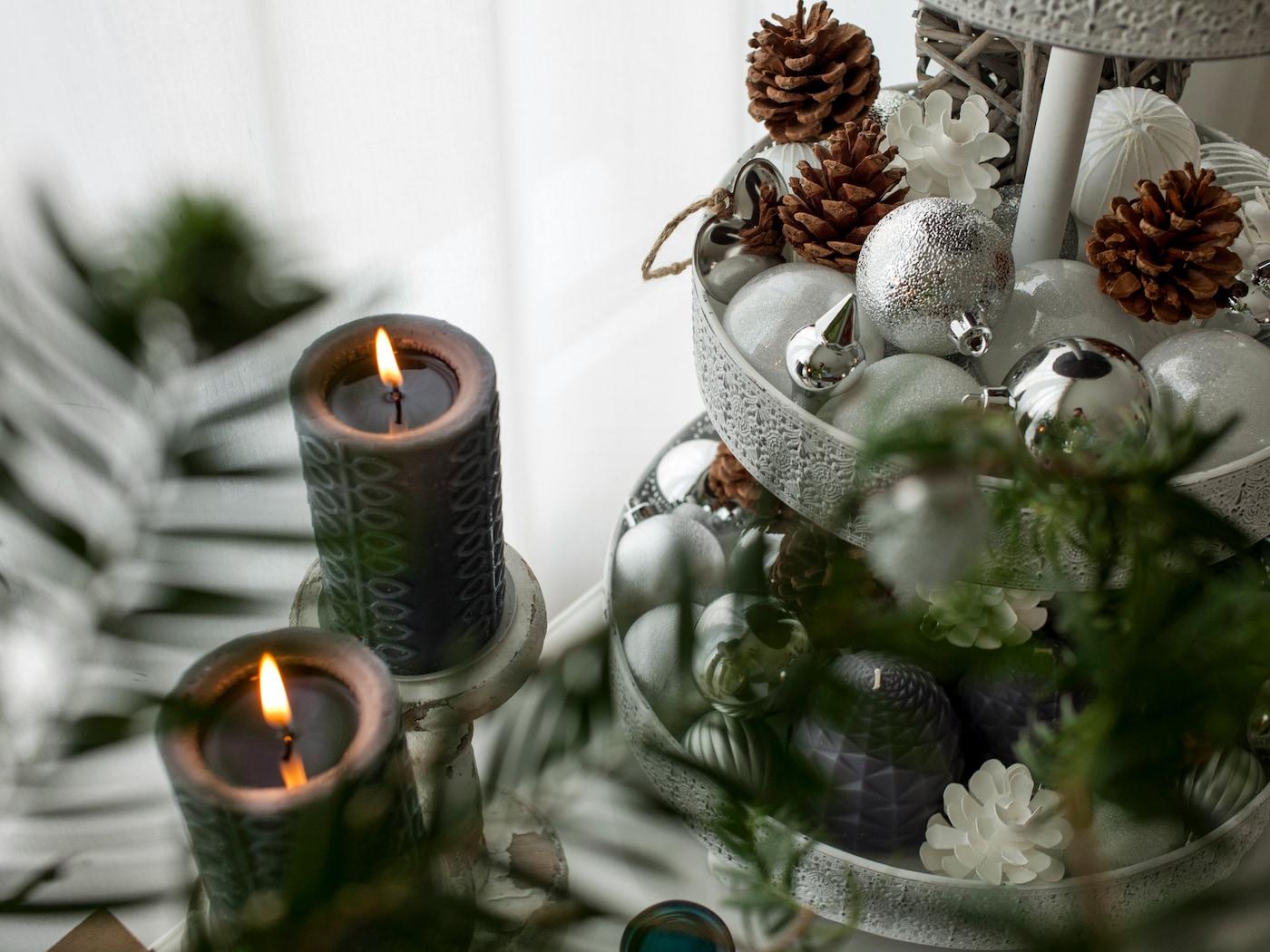 Eine Etagere von IKEA gefüllt mit weihnachtlicher Deko, daneben zwei brennende Kerzen