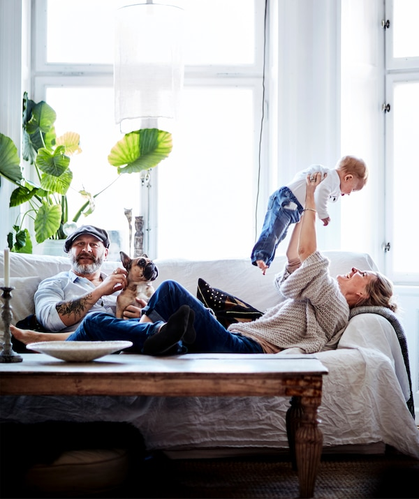 Eine Familie entspannt sich zusammen auf dem Sofa.