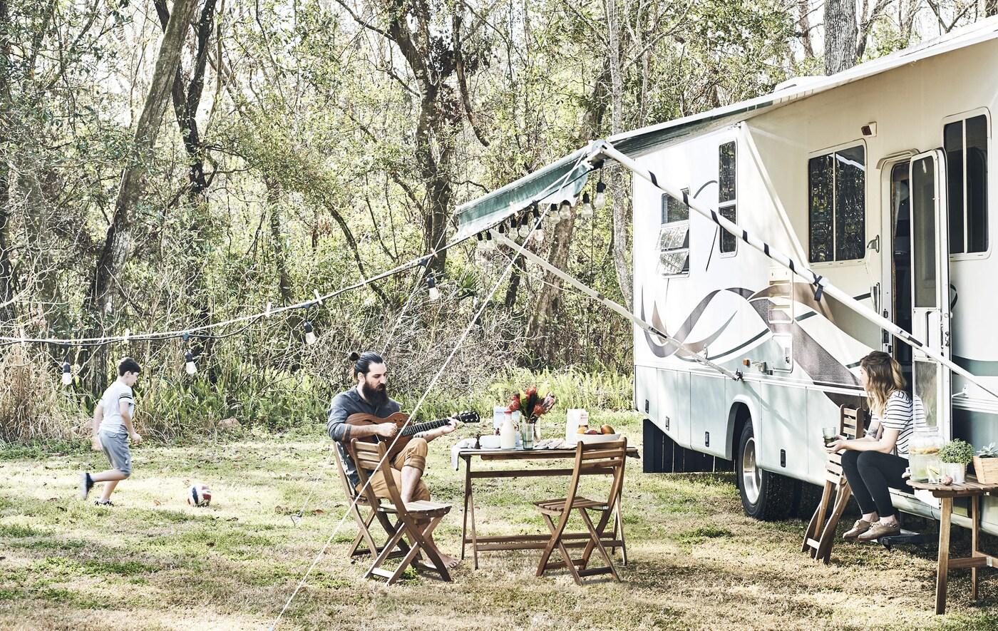 Eine Familie entspannt vor einem Wohnmobil in ländlicher Umgebung.