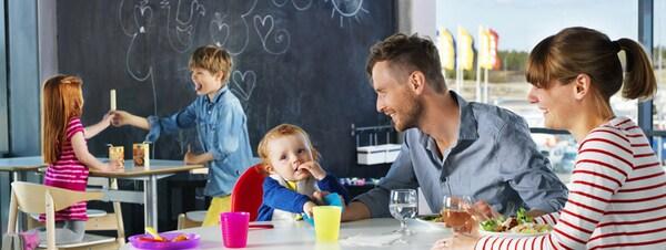 Eine Familie mit kleinem Kind sitzt gemeinsam in einem IKEA Kundenrestaurant, im Hintergrund spielen zwei Kinder