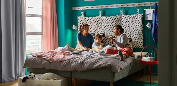 Eine Familie mit Mutter, Vater und Kind sitzt auf dem Bett und spielt.