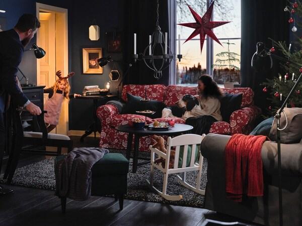 Eine Familie sitzt im weihnachtlich geschmückten Wohnzimmer