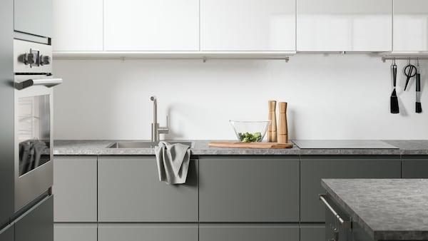 Eine fertig montierte IKEA-Küche mit grauen Unterschränken und weissen Wandschränken