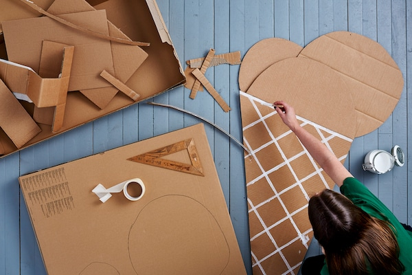Eine Frau bastelt mit Karton & bemalt den Karton in Eiswaffel-Form mit weißer Farbe.