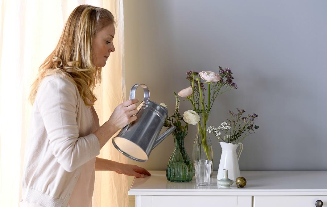 Eine Frau, die Wasser in einer Blumenvase nachfüllt