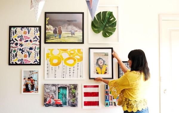 Eine Frau gestaltet gerade ihre Bilderwand, die aus Bildern, Fotos und Kunstwerken besteht.