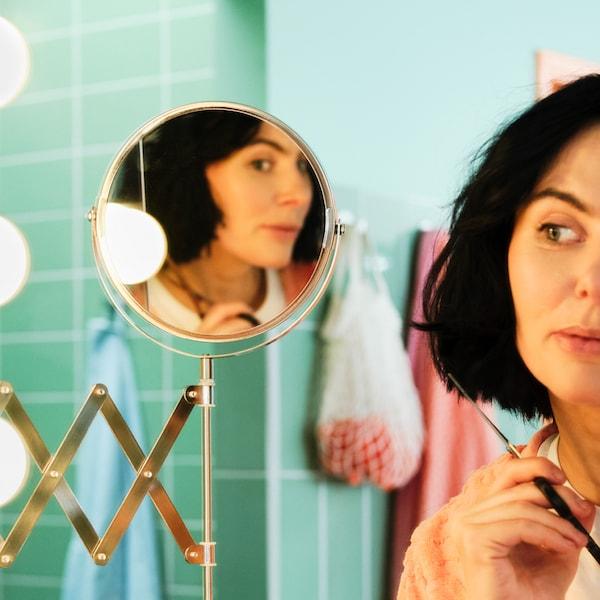 Eine Frau hält in einem grün gefliesten Bad eine Schere in der Hand und schaut in einen FRÄCK Spiegel, während sie sich die Haare schneidet.