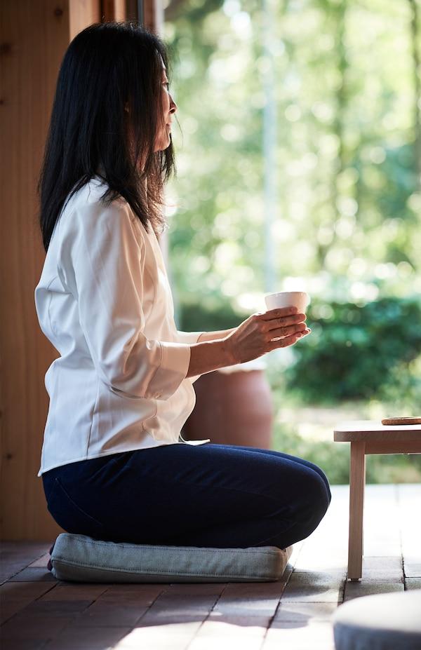 Eine Frau hält mit beiden Händen einen Becher, während sie auf einem OMTÄNKSAM Stuhlkissen sitzt.