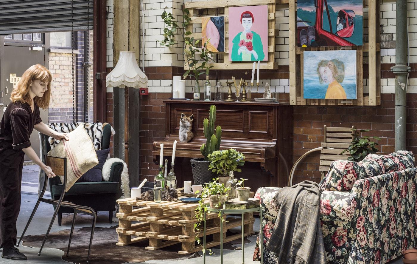 Eine Frau in einem Innenhof mit geblümten Sofa, Tisch aus Paletten & Holzklavier & bunten Bildern