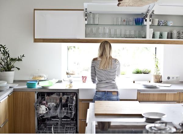 Eine Frau in einer braun-weißen Küche mit offener Spülmaschine & geschlossenen Schränken