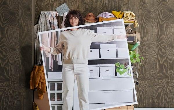 Eine Frau in heller Kleidung steht vor einer Aufbewahrung mit Boxen, Kleidung und Pflanzen.