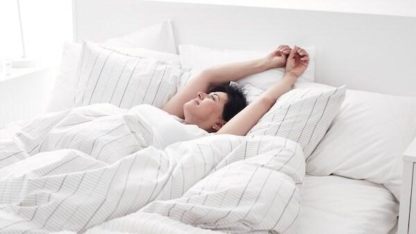 Eine Frau ist im Bett und streckt sich