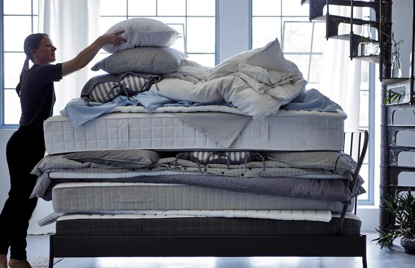 Eine Frau legt ein Kissen auf einen Stapfel weicher Matratzen, Bettdecken und Bettwäsche.
