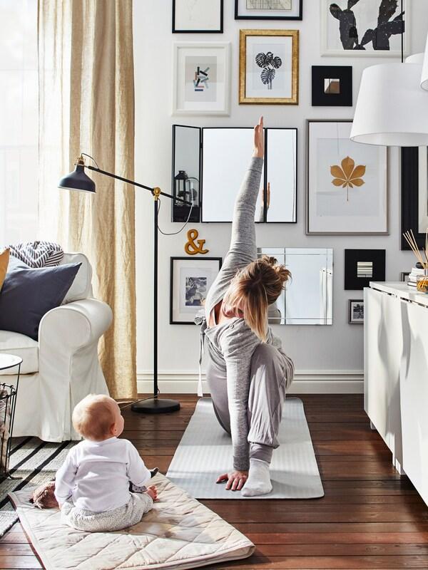 Eine Frau macht Yoga auf einer Gymnastikmatte im Wohnzimmer. Ein Baby sitzt auf einer Matte daneben und beobachtet sie, u. a. mit einem Sofa, einem Sessel und einer Bilderwand in der Nähe.