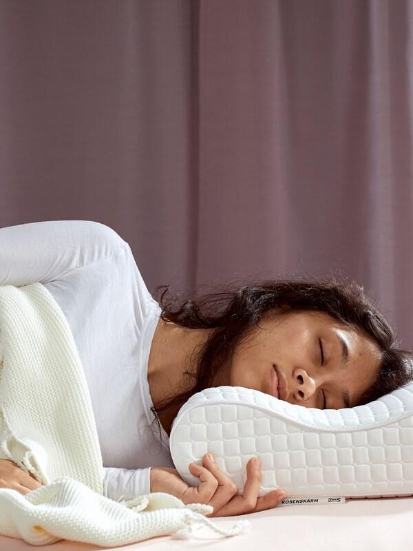 Eine Frau mit braunem Haar und einem weißen Pulli schläft unter einer weißen Decke auf einem ROSENSKÄRM ergonomischen Kopfkissen.