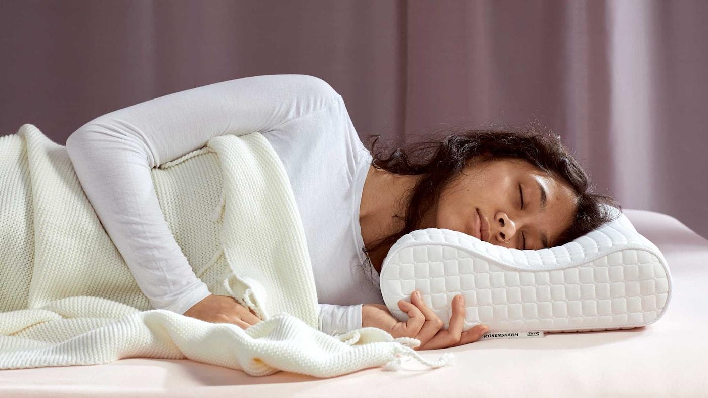 Eine Frau mit braunem Haar und einem weissen Pulli schläft unter einer weissen Decke auf einem ROSENSKÄRM ergonomischen Kopfkissen.