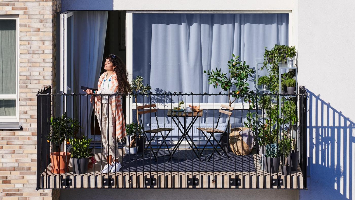 Eine Frau mit langen, dunklen Haaren steht auf dem Balkon einer Wohnung, auf dem Topfpflanzen, ein Tisch und Stühle zu sehen sind.