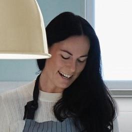 Eine Frau mit Schwarzen Haaren spricht um damit ihre smarten Geräte zu steuernt.