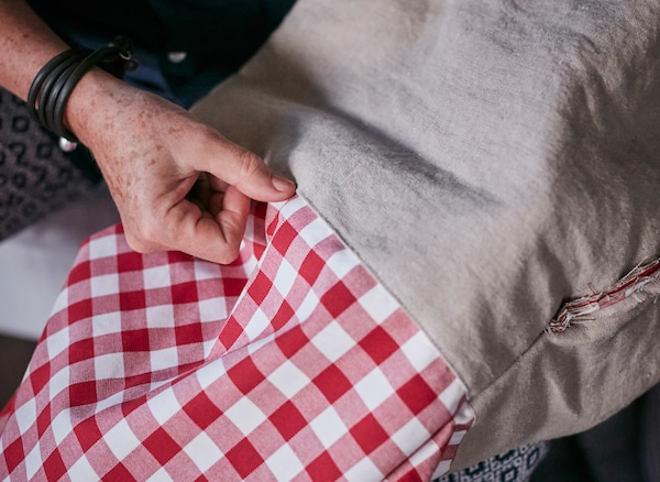 Eine Frau näht einen Geschenkbeutel aus BERTA RUTA Meterware kariert in Rot.