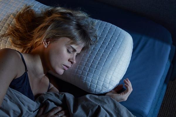 Eine Frau schläft auf einem ergonomischen, kühlenden Kopfkissen
