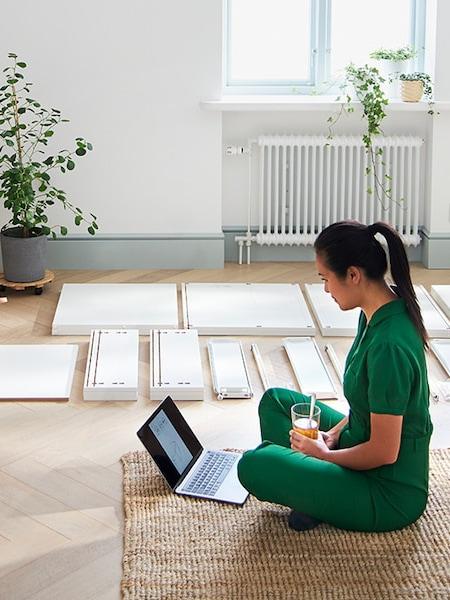 Eine Frau sitzt am Boden und baut ein Regal von IKEA zusammen. Vor ihr steht ein Laptop