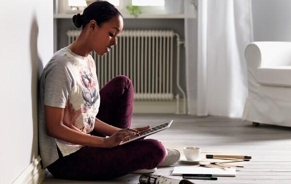 a53501bce2c6ee Eine Frau sitzt auf dem Wohnzimmerboden und sieht sich die IKEA Website auf  ihrem Tablet an