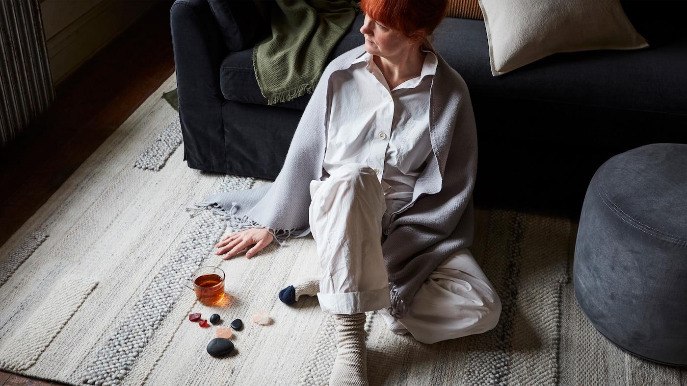 Eine Frau sitzt auf einem handgewebten BRÖNDEN Teppich in Beige. Sie lehnt an ein dunkelgraues FÄRLÖV Sofa mit Kissen und einem Plaid. Neben ihr steht ein grauer Hocker.