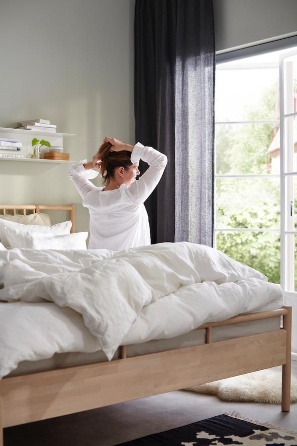 Eine Frau sitzt auf ihrem Bett mit weißer Bettwäsche und fährt sich durch die Haare