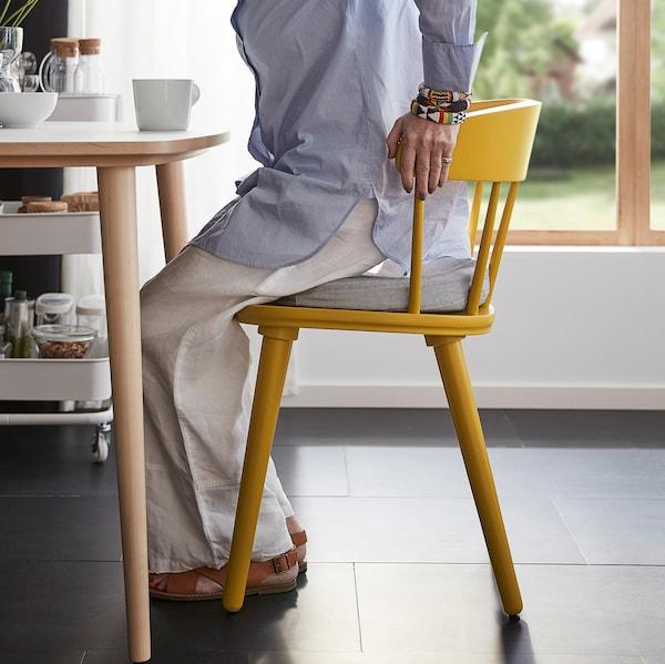 Eine Frau steht von einem OMTÄNKSAM Stuhl auf, indem sie sich an der hohen Rückenlehne festhält. Die abgerundete Rückenlehne und Sitzfläche sorgen für zusätzliche Bequemlichkeit.