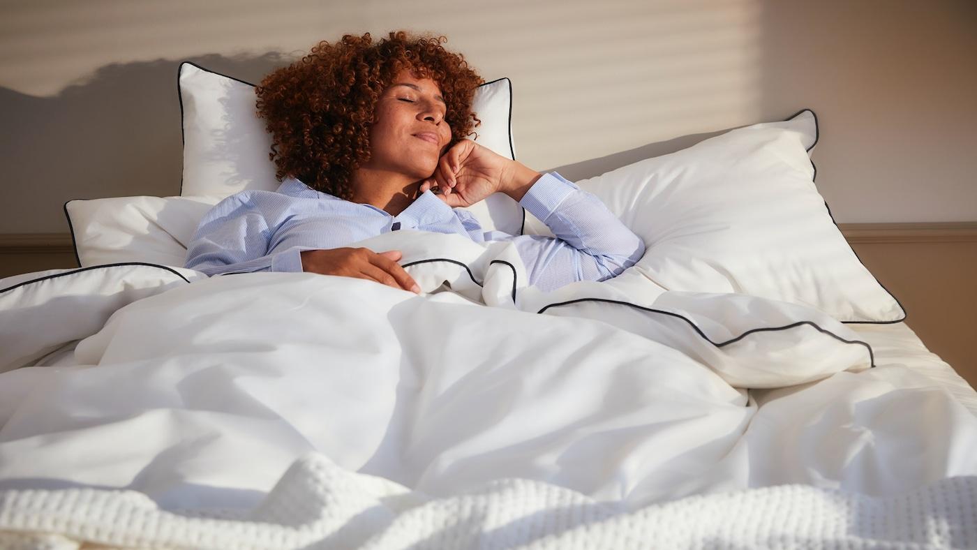 Eine Frau streckt sich während sie im Bett liegt