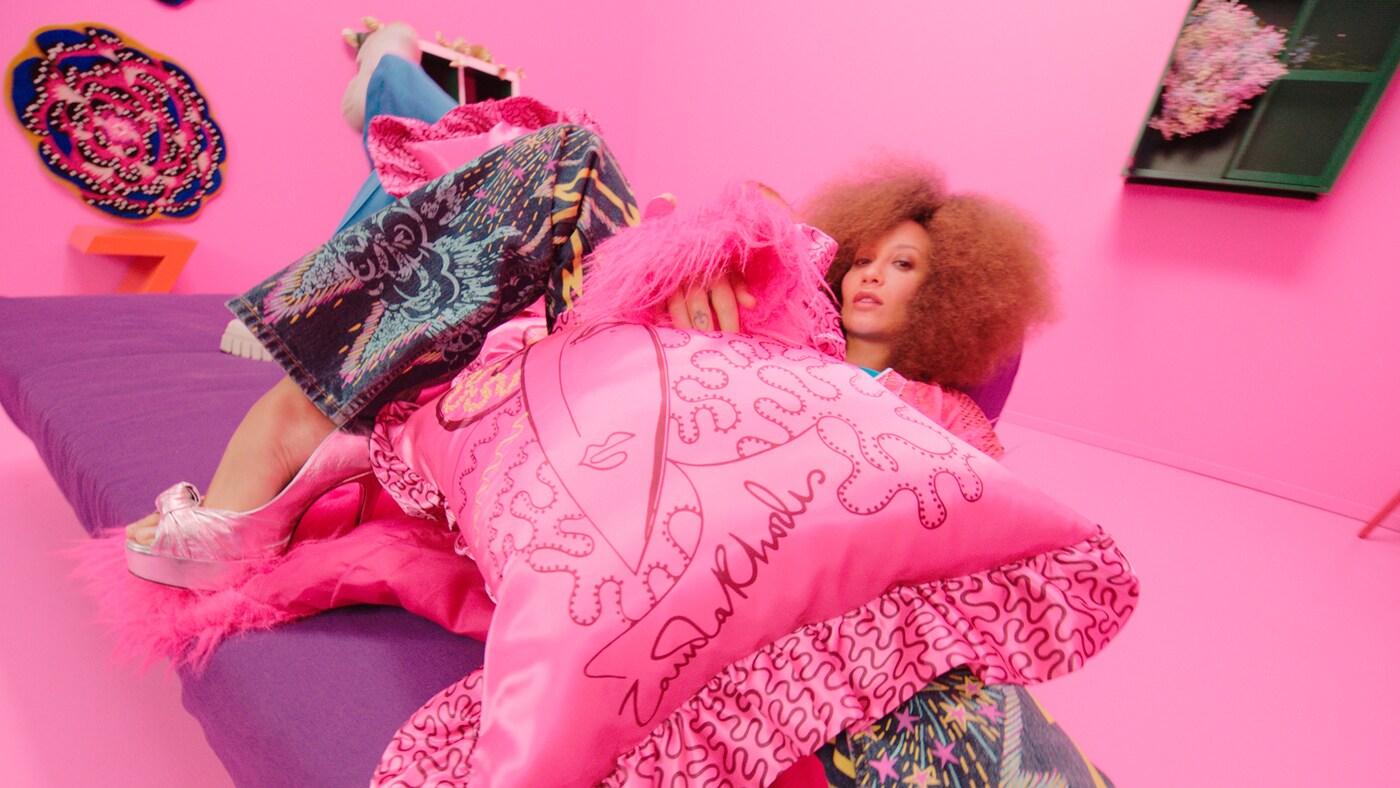 Eine Frau tanzt in einem rosafarbenen Raum und spielt mit Accessoires aus der KARISMATISK Kollektion.