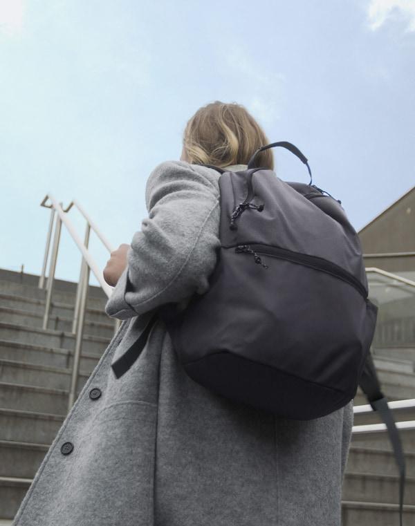 Eine Frau trägt einen dunkelgrauen VÄRLDENS Rucksack auf dem Rücken, während sie eine Treppe hinaufsteigt.