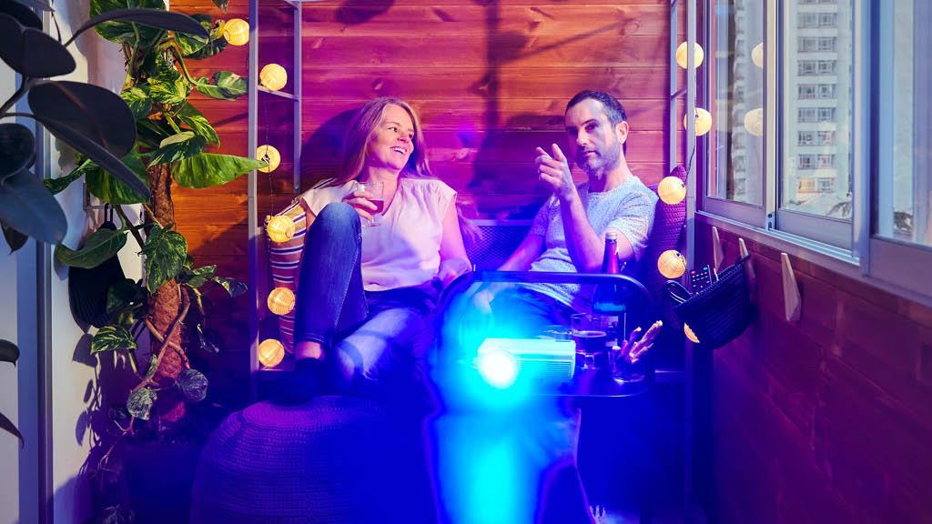 Eine Frau und ein Mann sitzen auf einer SVANÖ Bank mit Rankgitter. Vor ihnen läuft ein Filmprojektor.
